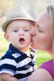 Glückliche Mutter, die nettes Baby küsst stockbild