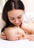 Glückliche Mutter, die schlafendes Baby betrachtet Lizenzfreie Stockfotografie