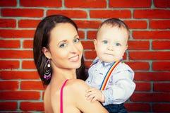 Glückliche Mutter, die seinen Sohn hält Stockfotografie