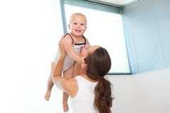 Glückliche Mutter, die zu Hause herauf nettes Baby anhebt Lizenzfreie Stockfotografie