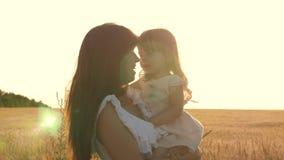 Glückliche Mutter geht mit dem Baby in ihren Armen auf einem Gebiet mit Weizen Tochter hält Mutter durch den Kasten, den die Fami stock footage