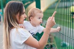 Glückliche Mutter hält netten lächelnden Sohn im Park stockbilder