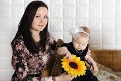 Glückliche Mutter hält Sonnenblume und zeigt sie ihrer kleinen Tochter Stockbilder