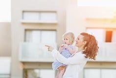 Glückliche Mutter mit dem Baby, das vor Wohnungsbau steht stockbilder