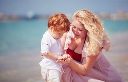 Glückliche Mutter mit dem Babysohn, der mit Kieselsteinen auf dem Strand, Sommerferien spielt lizenzfreie stockfotos