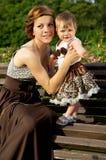 Glückliche Mutter mit einem Baby auf der Bank Stockfoto