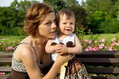 Glückliche Mutter mit einem Baby auf einem Bankrest Stockbild