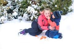 Glückliche Mutter mit ihrem Sohn in einer Armumarmung auf dem Schnee mit einer Mandarine Lizenzfreie Stockbilder