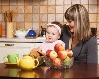 Glückliche Mutter mit ihrer kleinen Tochter, die zu Mittag isst Lizenzfreie Stockfotos