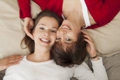 Glückliche Mutter mit ihrer Tochter, die auf dem Bett stillsteht Lizenzfreie Stockfotografie