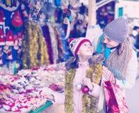 Glückliche Mutter mit kaufenden Dekorationen der freudigen kleinen Tochter für Lizenzfreie Stockfotografie