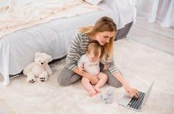 Glückliche Mutter mit Kind auf Teppich lizenzfreie stockfotografie