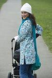 Glückliche Mutter mit Kinderwagen im Park Lizenzfreies Stockbild