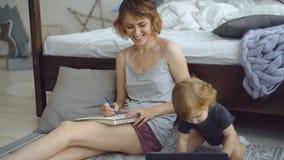 Glückliche Mutter mit netter entzückender Tochterzeichnung im Album mit den Bleistiften, die zu Hause nahe Bett sitzen Stockbild