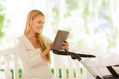 Glückliche Mutter mit Tabletten-PC und -Spaziergänger im Park Stockfoto