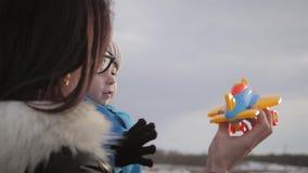 Glückliche Mutter mit wenigem Sohn, der mit Spielzeugfläche bei Sonnenuntergang spielt Attraktive Mutter und Kind, die Spielwaren stock video