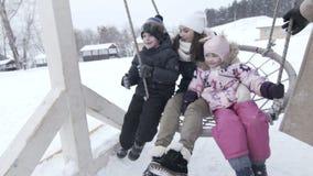 Glückliche Mutter mit zwei Kindern auf großem Schwingen im Winter, slowmotion stock video