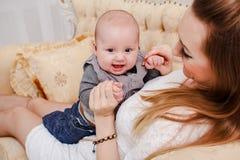Glückliche Mutter umarmt halb-Jahr-altes Baby Stockfotografie