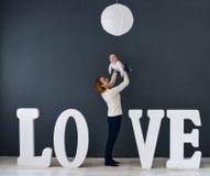 Glückliche Mutter und Baby des Porträts, auf grauem Hintergrund nahe großen Buchstaben der Wortliebe Stockfoto