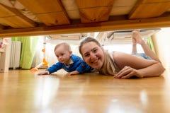 Glückliche Mutter und Baby, die auf Boden liegt und unter dem b schaut Lizenzfreie Stockfotos