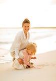 Glückliche Mutter und Baby, die auf dem Strand spielt Lizenzfreie Stockfotos