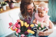 Glückliche Mutter und Baby, die Dekoration mit Blumenstrauß von Tulpen macht lizenzfreie stockbilder