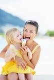 Glückliche Mutter und Baby, die Eiscreme isst Stockbild
