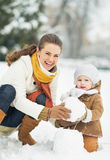 Glückliche Mutter und Baby, die Schneemann im Winterpark macht stockfotos