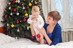 Glückliche Mutter und Baby, die Weihnachtsball hält Stockfotos