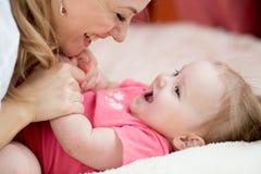 Glückliche Mutter und Baby haben Spaßzeitvertreib zu Hause lizenzfreies stockbild