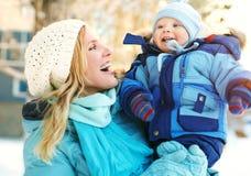 Glückliche Mutter und Baby im Winterpark Lizenzfreies Stockfoto