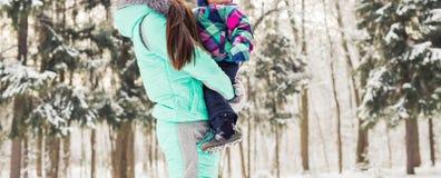 Glückliche Mutter und Baby im Winterpark Familie draußen nette Mama mit ihrem Kind Lizenzfreies Stockbild