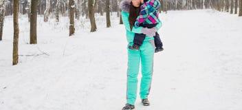 Glückliche Mutter und Baby im Winterpark Familie draußen nette Mama mit ihrem Kind Lizenzfreies Stockfoto