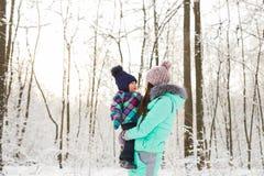 Glückliche Mutter und Baby im Winterpark Familie draußen nette Mama mit ihrem Kind Lizenzfreie Stockfotos