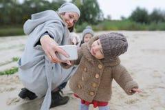 Glückliche Mutter und Baby mit ihrem Welpen, der selfie auf Herbstsee macht Lizenzfreie Stockfotografie