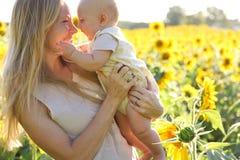 Glückliche Mutter-und Baby-Tochter im Sonnenblumenfeld stockfotos