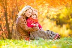 Glückliche Mutter und das Kind, die im Herbst im Freien ist, parken stockbild