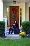 Glückliche Mutter und der Sohn, die auf dem Portal des Herbstes sitzt, verzierten Haus Stockfotos