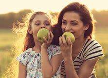 Glückliche Mutter und der Spaß, die Kindermädchen genießt, haben ein Picknick und ein Essen Stockfotografie
