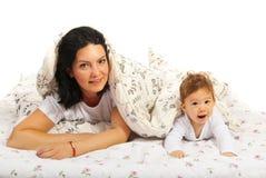 Glückliche Mutter und ihr Baby im Bett Stockfotografie