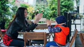Glückliche Mutter und ihr kleiner Sohn, die über das Stadtcafé spielt und lacht stock video footage