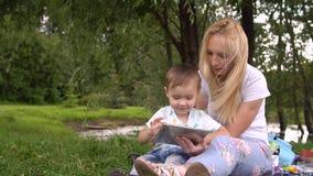 Glückliche Mutter und ihr kleiner Sohn, die das Spielen auf Tablet-Computer im Park genießt stock footage