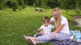 Glückliche Mutter und ihr kleiner Sohn, die das Spielen auf Tablet-Computer im Park genießt stock video footage