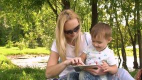 Glückliche Mutter und ihr kleiner Sohn, die das Spielen auf Tablet-Computer im Park genießt Langsame Bewegung stock video