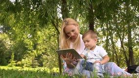 Glückliche Mutter und ihr kleiner Sohn, die das Spielen auf Tablet-Computer im Park genießt Langsame Bewegung stock video footage