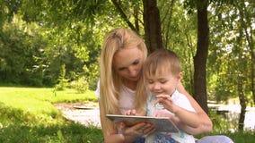 Glückliche Mutter und ihr kleiner Sohn, die das Spielen auf Tablet-Computer im Park genießt Langsame Bewegung stock footage