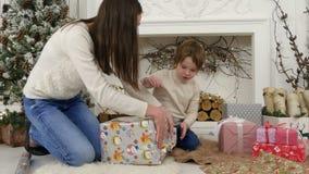 Glückliche Mutter und ihr kleiner Sohn, die oben zu Hause Weihnachtsgeschenke einwickelt stock video footage