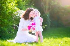 Glückliche Mutter und ihre lustige Tochter im Garten Lizenzfreie Stockbilder
