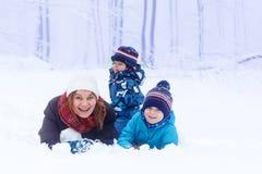 Glückliche Mutter und ihre Söhne mit zwei Kleinkindern, die mit Schnee spielen Stockbild