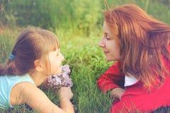 Glückliche Mutter und ihre Tochter liegen auf dem Gras gegen jedes othe Lizenzfreie Stockfotografie
